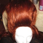 "Back to the front. Take that 1"" thickness of hair that you didn't tease/pin up. Comb it and smooth it over the form and the teased hair so that you have a smooth outer layer. Pin it at that same point in the top. Hairspray it as if your life depended on it. Start with the center of your hairline..."